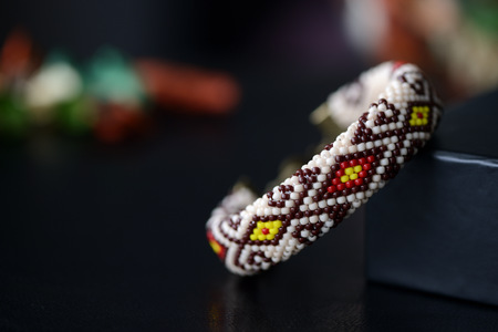 Beige beaded bracelet with oriental pattern on a dark background close up