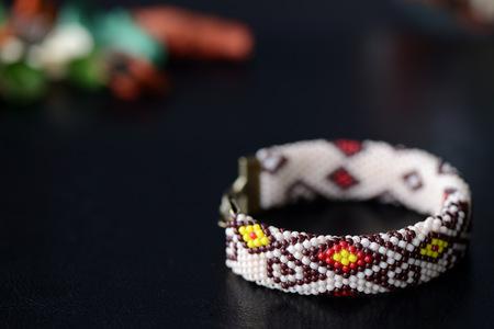 Beige beaded bracelet with oriental pattern on a dark background close up