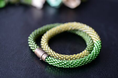 Bead crochet necklace three shades of green on a dark background close up
