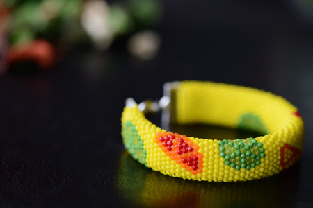 Bright yellow bracelet with citrus print on a dark background close up
