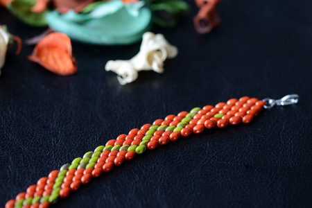 Beaded bracelet made of superduo beads on a dark background close up Stock Photo