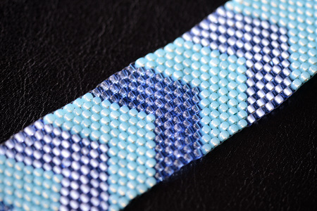 Beaded bracelet two shades of blue on a dark background close up