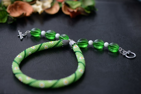 Green summer necklace with chamomile print on a dark background close up