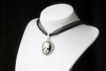 Halloween necklace with skeleton cameo pendant on a dark background close up