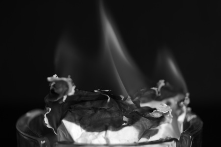 A piece of paper burning in a glass ashtray close up. Black and white Stock Photo