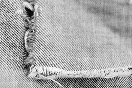 Old torn jeans texture and background close up. Black and white