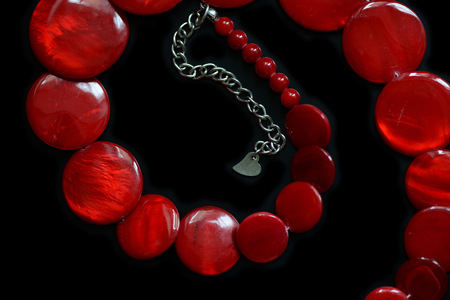 Red necklace from round flat beads on a dark background close up