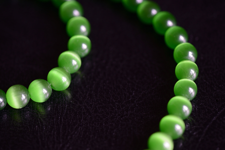 Green stone necklace on a dark background close up