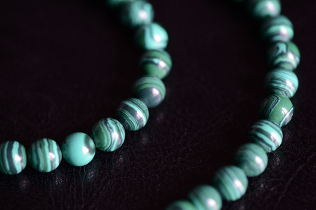 Malachite stone beads necklace on a dark background close up