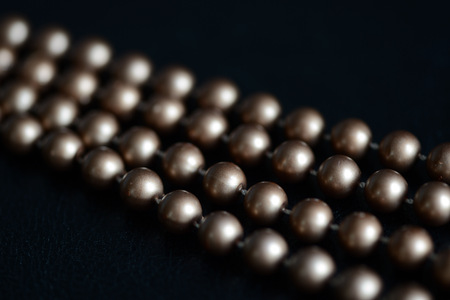 Long necklace of brown beads on a dark background close up