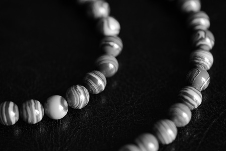 Malachite stone beads necklace on a dark background close up. Black and white