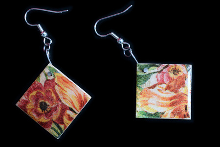 Wooden earrings with a floral print on a dark background close up
