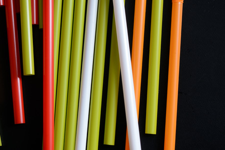 Colorful plastic straws on a dark background close up 免版税图像