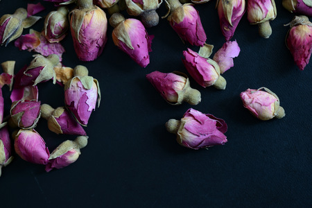 Dried rose buds scattered on a dark surface close up