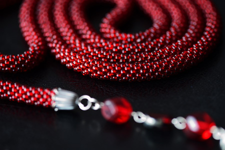 Lariat necklace red color with bead decoration on a dark background close up