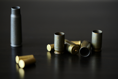 Empty old bullet cartridges on a dark background close up Imagens - 115637860