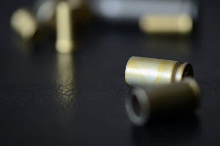 Empty old bullet cartridges on a dark background close up 写真素材
