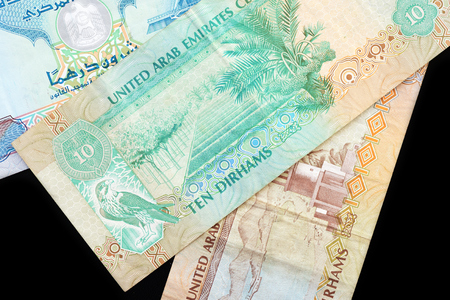UAE dirham currency notes on a dark background close up