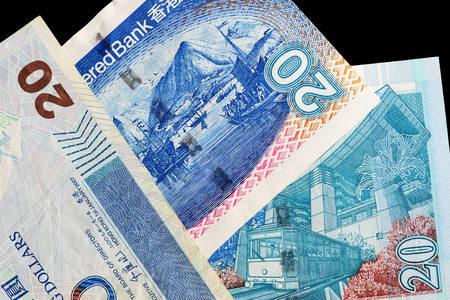 Three different bills in twenty Hong Kong dollars on a dark background close up