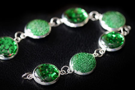 Resin bracelet with green sparkles on a dark background close up
