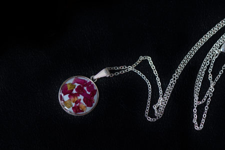 Resin pendant with dry rose petals on a dark background close up Imagens