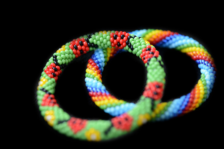 Two kid's summer bracelets made of seed beads isolated on a black background close up Imagens