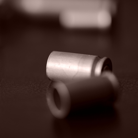 Old bullet cartridges on a dark background close up. Brown color toned Stock Photo