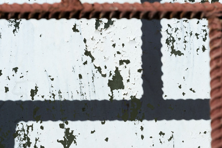 Old painted window behind iron bar close up. Grunge background