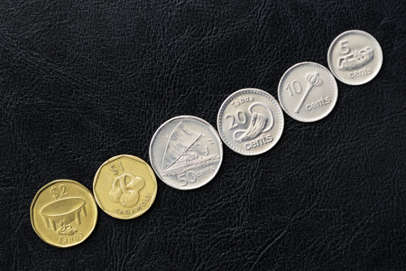 Several coins from Fiji on a dark background close up