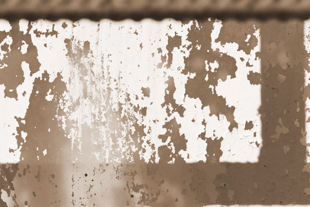 Old painted window behind iron bar close up. Grunge background in brown color Stock Photo