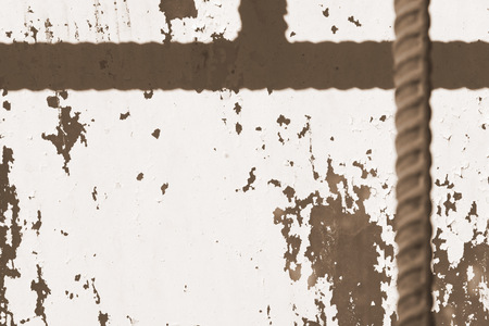Old painted window behind iron bar close up. Grunge background in brown color Banco de Imagens