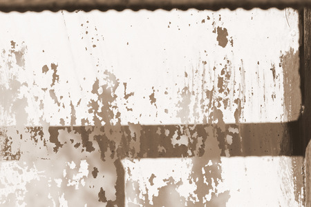 Old painted window behind iron bar close up. Grunge background in brown color