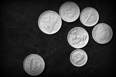 Several Fiji coins on a dark background close up. Black and white 스톡 콘텐츠