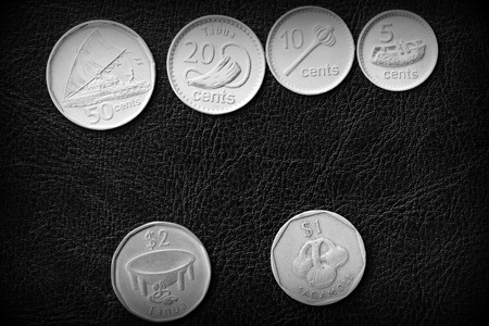 Several Fiji coins on a dark background close up. Black and white