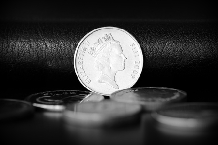 Ten fijian cents on a dark background close up. Black and white Imagens