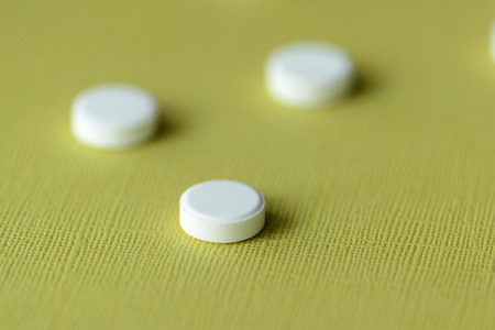 White tablets scattered on a green-yellow background close up