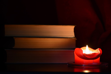 Red burning candle and old books in the dark close up Standard-Bild