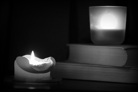 Burning candle and old books in the dark close up. Black and white