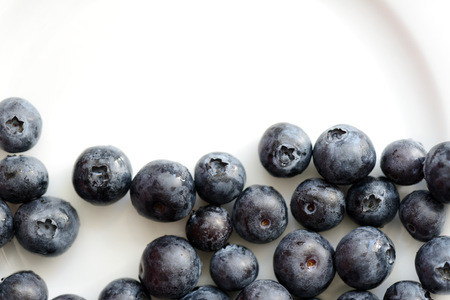 Fresh blueberry berries on a white plate close up. Top view