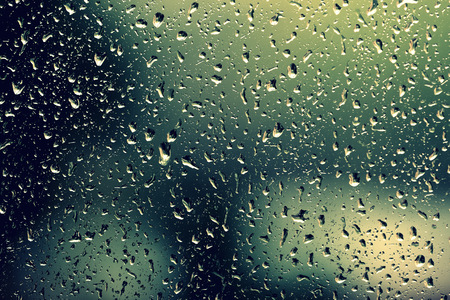 Water drops on glass during a rain close up. Natural background