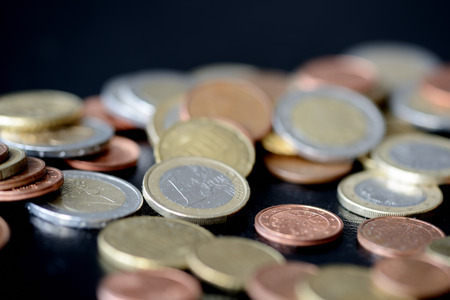 Pile of Euro coins scattered on a dark surface close up