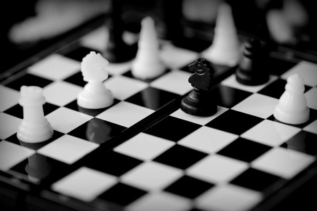 Travel Chess on a dark background close up. Black and white