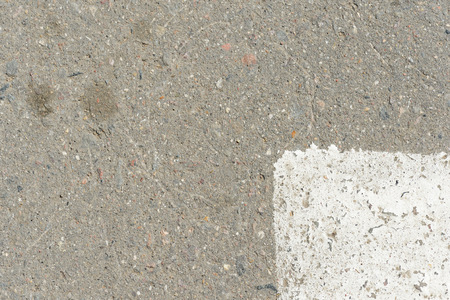 Old asphalt surface with white paint on it close up. Abstract background