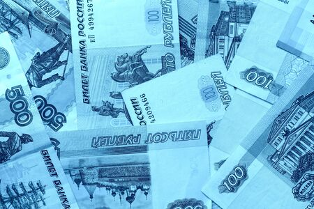Different bills of Russian rubles close up. Money background blue color toned