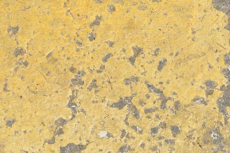 Old asphalt surface with yellow paint on it close up. Abstract background