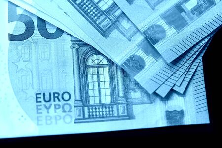 Fifty euro notes on a dark background close up. Blue color toned Stockfoto