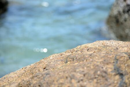 Closeup view of sea stone on a background of blue sea