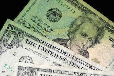 Dollar bills on dark background close up. Money background green color toned