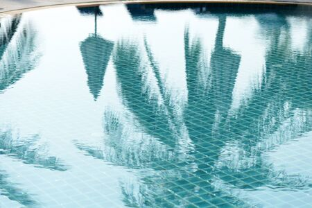 Reflections of palm trees and beach umbrellas in the pool in the morning. Blurred abstract background 免版税图像