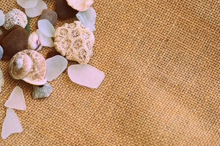Shells, sea glasses and stones on a jute background close-up brown color toned. Vacation concept